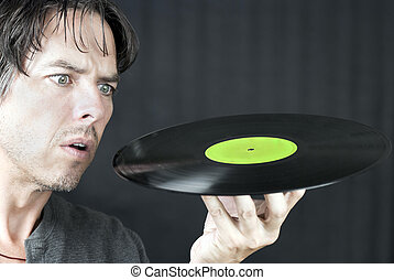 Man Looks At LP In Confusion - Close-up of a man looking at...