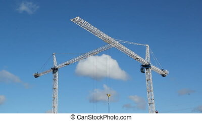 Two cranes. - White tower cranes against blue sky. Trolley...