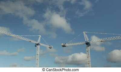 Two cranes. Timelapse. - White tower cranes against blue...