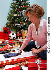 Woman sat wrapping Christmas presents.