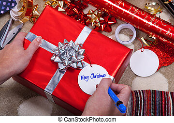 Woman writing a tag for her Christmas presents.