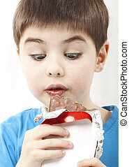 Surprised boy with chocolate - Image of the surprised boy...