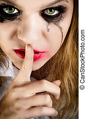 A scary looking young woman showing silence