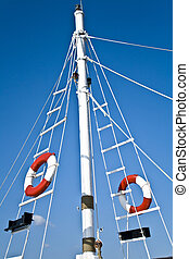 Sailing mast with life buoy over blue sky