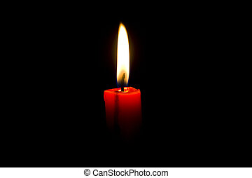 Closeup of burning red candle isolated on black background