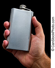 Hip flask  in man's hand on a black background.