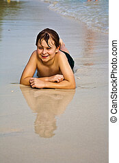 young boy is lying at the beach and enjoying the warmness of...