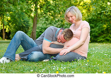 Pregnant couple in the park - Pregnant couple resting in the...