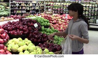 Choosing Apples - Teen girl choosing apples in produce...