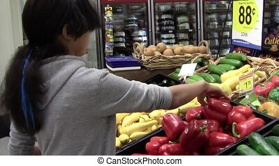 Choosing Peppers - Teen girl choosing peppers in produce...
