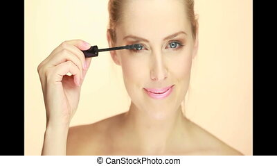 woman applying mascara closeup