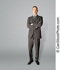 smiling standing businessman in suit isolated on gray