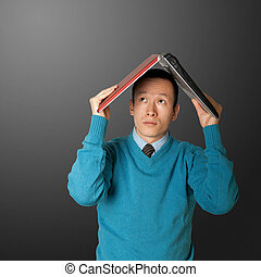 young businessman hides under the laptop - young asian...