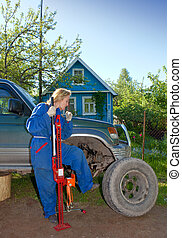 The woman in working overalls tries to replace a wheel at an...