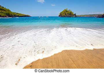 View from a sandy beach on rocks at ocean. Indonesia, Bali...
