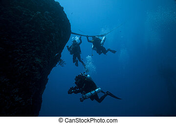 Divers Descending - Three technical divers descending to the...