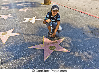 boy at the Walk of Fame sitting at the star for The simpsons...