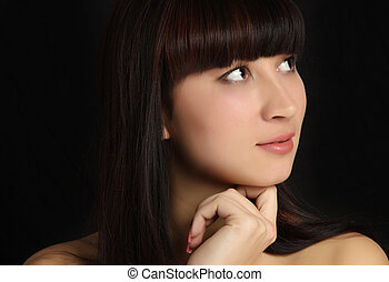 Beautiful thoughtful woman looking up on a black background