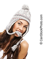 young brunette woman holding part of her winter cap with her mouth on white background