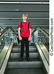 boy on a moving staircase inside the airport