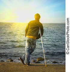 Yang man hiking on crutches on the beach