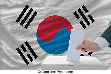 man voting on elections in south korea in front of flag -...