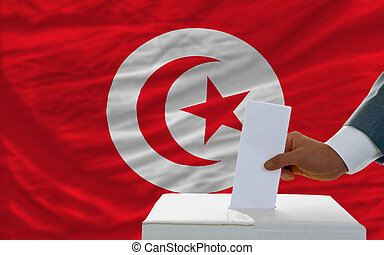 man voting on elections in tunisia in front of flag - man...