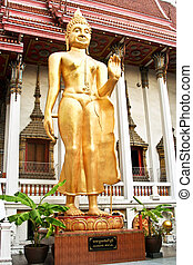 standing Buddah in a temple in Bangkok is giving a handsign