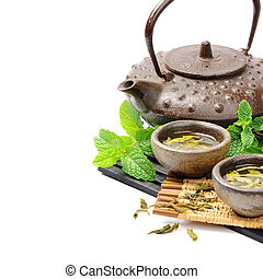Asian tea set with dried green tea and fresh mint over white