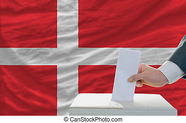 man voting on elections in denmark in front of flag - man...
