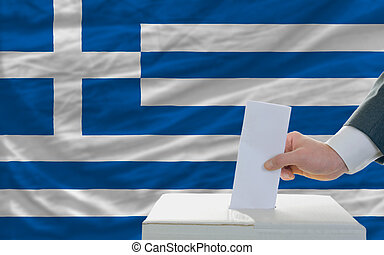 man voting on elections in greece in front of flag - man...
