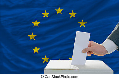 man voting on elections in europe in front of flag - man...