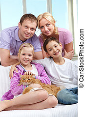 Family with pet - A young family of four with a cat sitting...