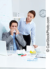 Blowing nose - Image of ill businessman sneezing while his...