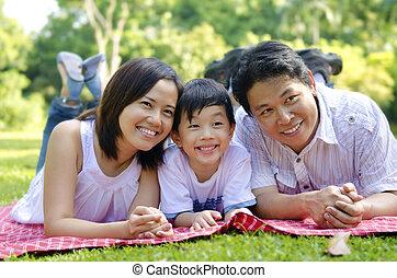 Happy family - Outdoor happy Asian family lying on floor