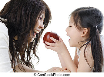 Healthy eating - Mother and daughter sharing an apple on...
