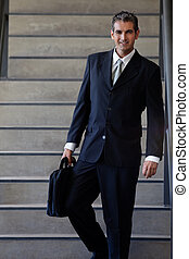 Male Entrepreneur Walking Down Stairs - Portrait of smart...