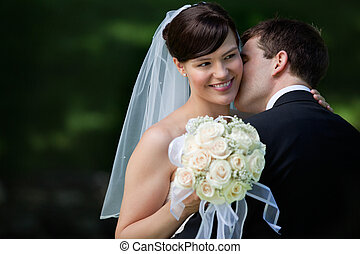 Happy Kiss of Newlyweds - Young groom kissing on cheek...