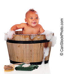 Baby in the Suds - An adorable biracial baby happily taking...