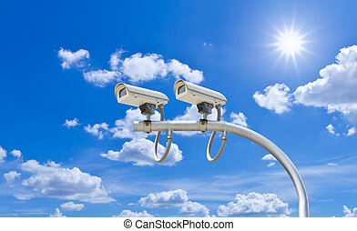 surveillance cameras against blue sky