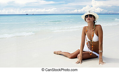 Attracrive girl sitting on the sand of a tropical beach -...