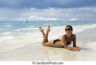 attractive female in a bikini lying on a tropical beach
