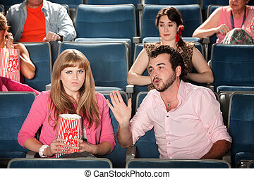 Man Talks to Woman in Theater - Young man talks out loud...