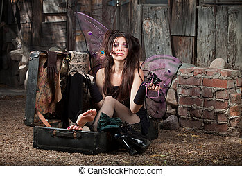 Worried Fairy - Worried Caucasian fairy with clothes sits in...