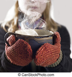 woman and hot steaming cup - detail of a woman with woolen...