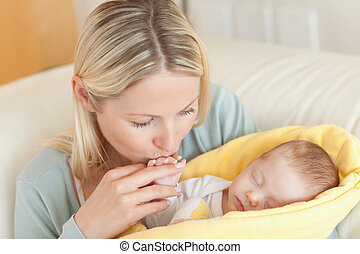 Mother on the sofa kissing her babys hand - Young mother on...