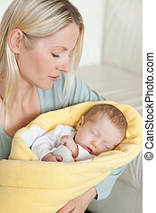 Mother holding her sleeping baby that is wrapped up in a cover