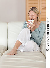Woman on the sofa taking a sip of coffee