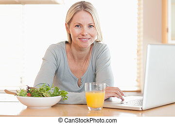 Woman having healthy lunch while working on her notebook -...