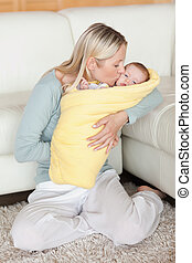 Mom kissing her baby that is wrapped into a cover